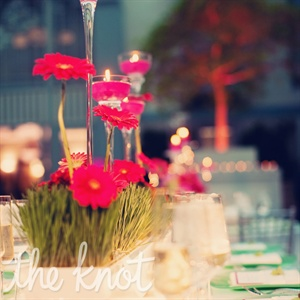 A long strip of grass with hot-pink daisies and elevated candles popping out had the fun look Ashley wanted.