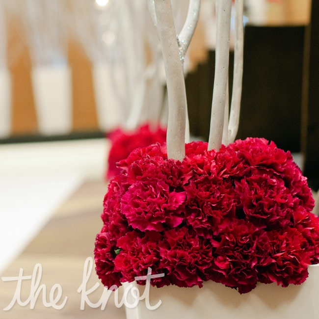 Mounds of bright carnations livened up the white ceremony aisle.