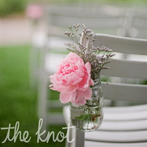 Mason jars filled with soft-pink peonies and greens hung from chairs that lined the ceremony aisle.