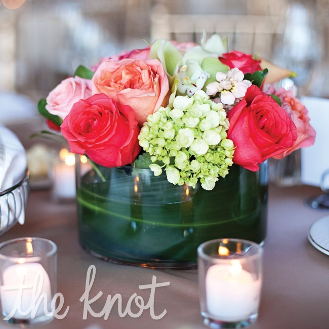 Low arrangements of pink and coral roses and green hydrangeas were held in simple glass vases.