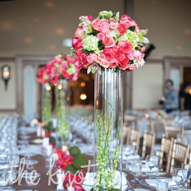"The banquet-style head table was decked out in tall ball-shaped centerpieces and scattered with plenty of green ""flower balls,"" petals and votive candlelight."