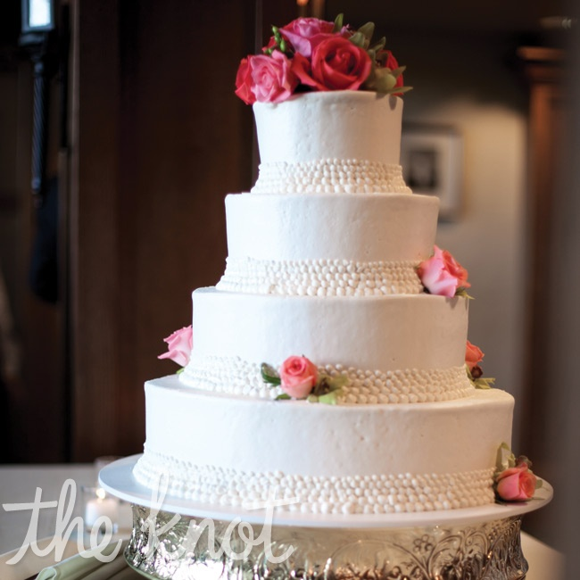 The four-tiered lemon cake was coated in vanilla buttercream frosting and topped with fresh roses.