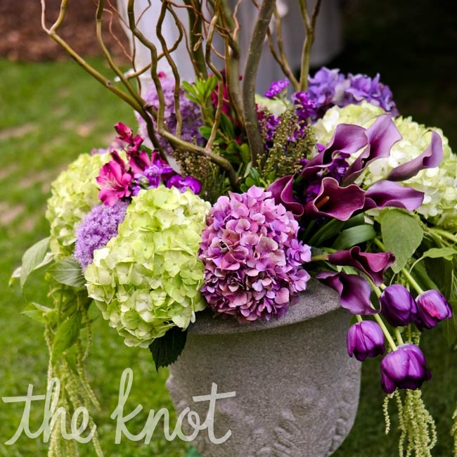 Stone vases filled with lush green and purple blooms were placed outside the reception tent.