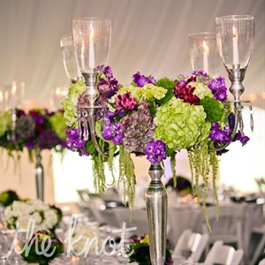 Silver antique-style candelabras were adorned in purple and green blooms.