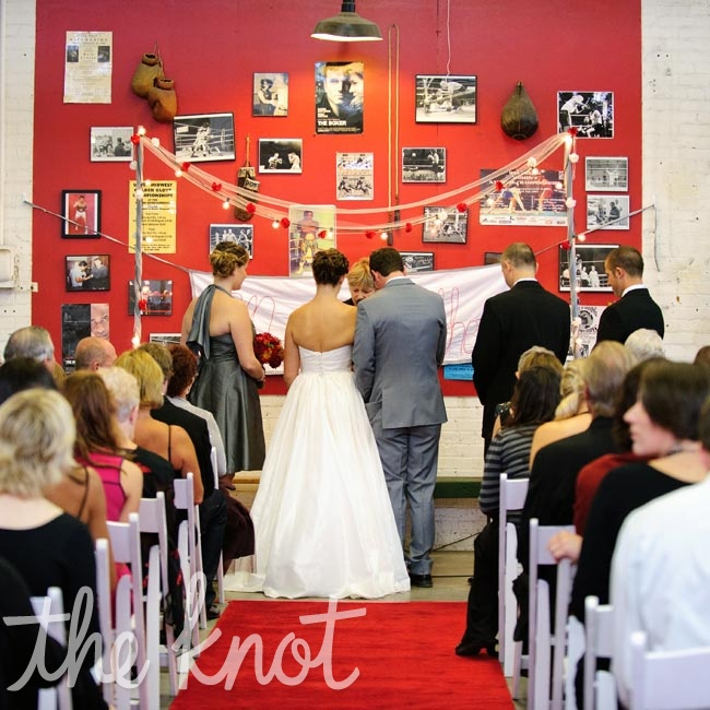 "A red carpet ""aisle"" led to the altar, which was draped in handmade garlands and Christmas twinkle lights."