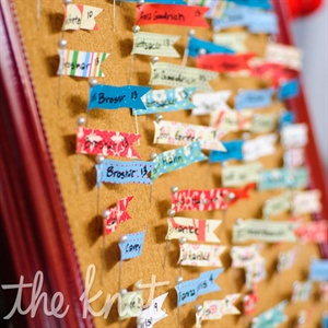 Flag-pin escort cards, tacked to a bulletin board, doubled as optional name tags for guests to wear.