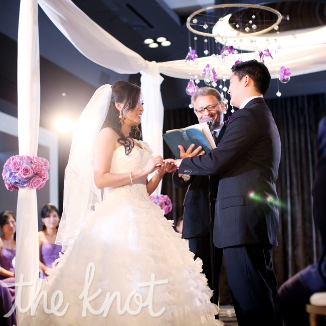 The couple exchanged vows beneath a modern center structure. It was draped in ivory accents, clear round circular shapes, flowers and crystals. Instead of the traditional two rows, seating was arranged in a circle around the couple.