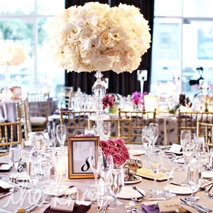 To give the room texture and flow, the couples florist created a mix of tall and low arrangements using monochromatic white and pinks flowers.