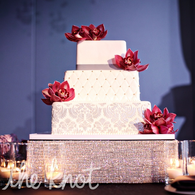 The cake was a true reflection of the couple's style: decorated with a light gray damask pattern and quilted Swiss dots. Bright red sugar flowers finished it off.