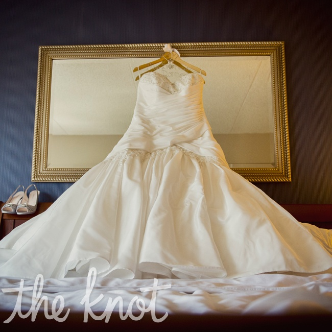 Megan wanted to wear a classic dress that wasn't plain. She found a taffeta modified A-Line gown in diamond white with criss-cross draping.