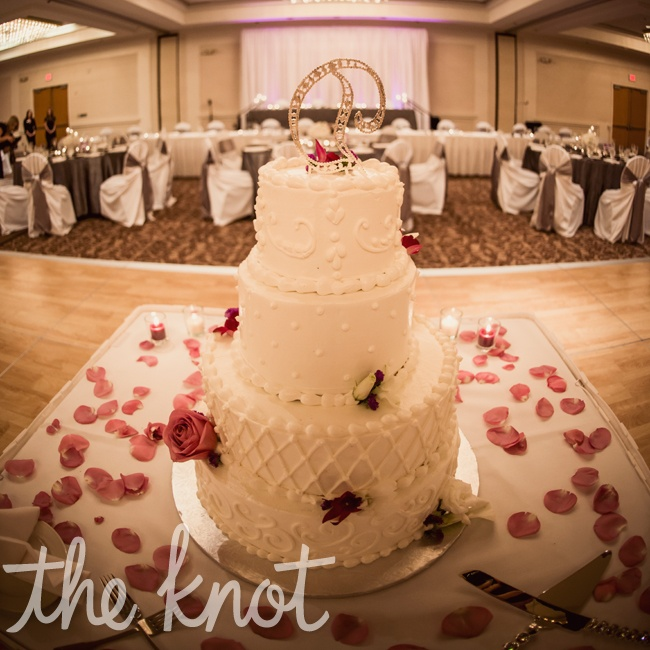 Megan Eric chose a different flavor for each layer of their four-tiered cake with buttercream frosting and decorated with scrollwork, dots, and swirl designs to accent the cake.