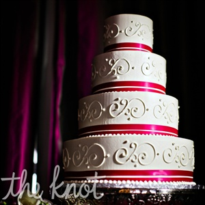 "Yoshi and Rosaleen wanted the cake to have a ""pop"" of color. They chose a four layer buttercream cake with dark raspberry ribbon and a strawberry cream filling for a ""surprise"" pop of color on the inside."