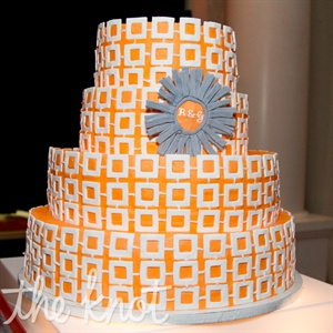 The orange and white cake was decorated with a geometric pattern and a gray accent with their initials.