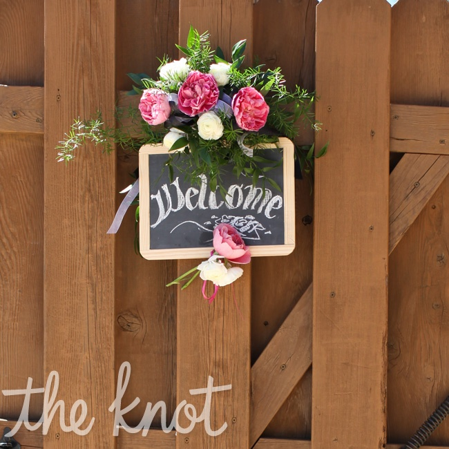 A chalkboard welcome sign decorated with pink garden roses greeted guests on their way in to the backyard.