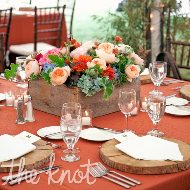 Wooden chargers (cut from a fallen tree) and burnt orange linens gave the tables a rustic and natural look.