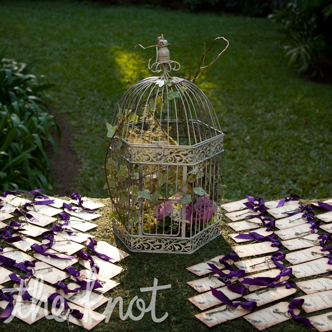 In keeping with the secret garden theme Natalie and Jason created escort cards with antique keys attached that were sourced in all various patterns from Etsy. Then cards featured a bird motif and were attached to the keys with plum colored ribbon.The cards were featured on a grass covered welcome table, which was decorated with a birdcage with a fl ...