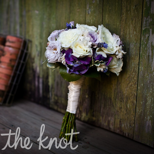 A combination of open white roses, tuberose blossoms, plum hydrangea, and pale lavender spray were round hand tied with ivory wrap for the bridal bouquet