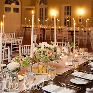 Lauren and Stephen wanted to create an intimate, romantic and relaxed atmosphere similar to a dinner party so they filled the reception space with candlelight and soft flowers. They decorated their farm tables with various sized vases and flowers.