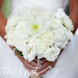 Ashley's all-white bridal bouquet included roses and ranunculuses. The flowers were wrapped together with burlap and tied off with a ribbon (that had come from her first communion veil).