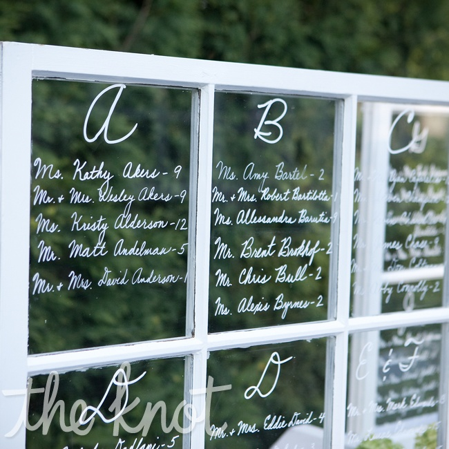 The mother of the groom created the seating chart by hand writing each guests' name on vintage window panels.