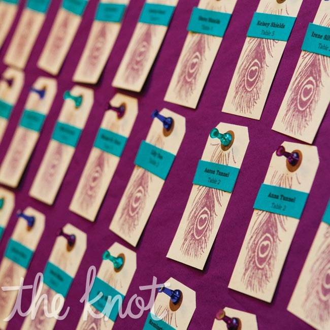 Colorful push-pins held the purple peacock-stamped escort cards to bulletin boards.