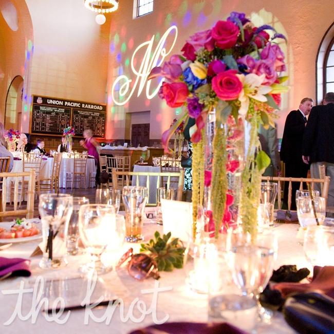 The centerpieces incorporated wrought iron candelabras filled with colorful roses and lilies on top of  lace linens. Megan and Anthony also incorpored a large 'M' script monogram gobo light on the wall and a professional light show and uplighting provided by their DJ.