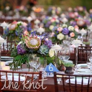 The tables were adorned with an assortments of desert inspired flowers, including succulents and king proteas. Potted succulents and candles surrounded each floral piece, and a soft pink and white geometric patterned runner stretched across each mahogany table.