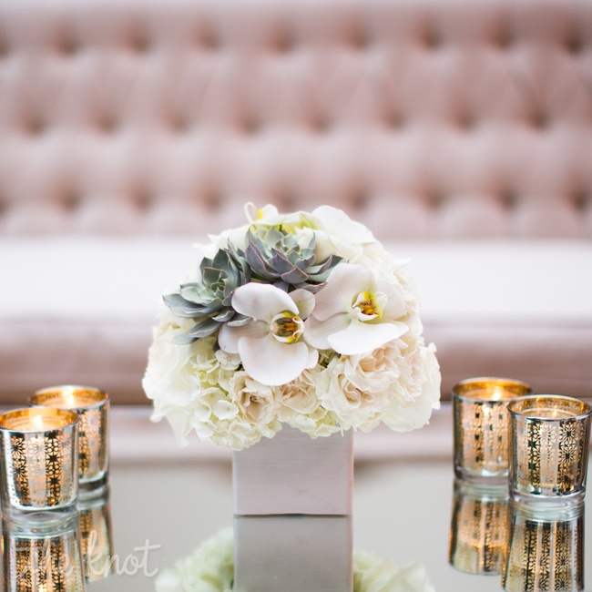 When it comes to design, there can be a fine line between conservative and stuffy; Savage successfully avoided crossing it by turning traditional elements on their ear. For arrangements that were anything but basic, succulents emerged unexpectedly from lush bouquets of classic white roses and tulips set in sculptural glass cylinders.