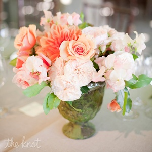 The centerpieces used a variety of aged-mossy garden stone containers filled with coral, papaya and pink tone wedding blossoms.  We included garden roses, ranuculus, peonies, sweet peas, and parrot tulips.