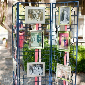 "The couple found a room divider with a Chippendale style at a discount store, painted it and displayed 8x10"" wedding pictures from each side of their family. It even included an engagement photo of Lauren and Ross."