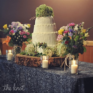 The cake was made by an aunt. It was lemon flavored with raspberry preserve and covered with buttercream. It was decorated with green hydrangeas and purple and green grapes. The cake stand was a huge slab of wood which was cut by Laura's dad.