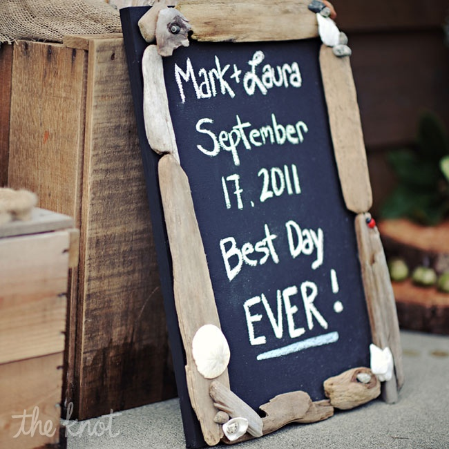 "Laura's mom had painted a piece of plywood with chalkboard paint and attached driftwood and rocks from the beach to the sign. Laura added ""Best day ever!"" and the sign is still on display in the couple's house."