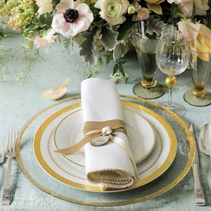 Something as simple as swapping the standard rentals for ornate dishware and posh linens can make a big impact. Gold detailing and a velvet tablecloth transform a traditional place setting into a regal setup fit for a king and queen.