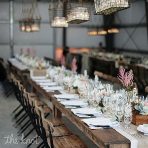 Crisp white place settings gave the wood farm tables, accented with white and burlap layered runners, a clean look
