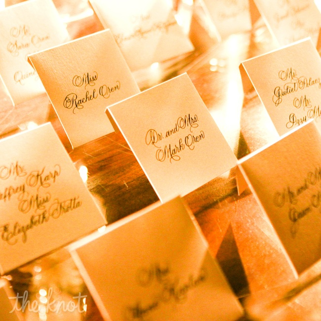 The height of formality: Escort cards tucked into beautifully calligraphed envelopes were surrounded by arrangements of tall branches