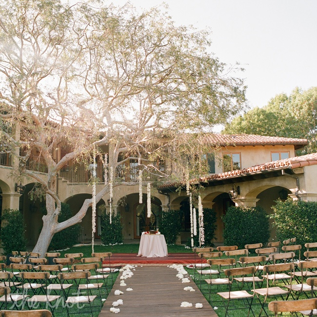Oren's team built a wooden walkway that led to a ceremony platform covered in vintage sari fabrics. Above, garlands of flowers hung from a tree, creating an artful interpretation of a huppah.