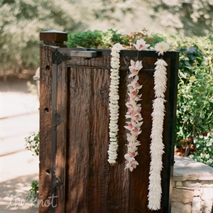 Guests were welcomed to the event by passing through a tall wooden gate decorated with three floral garlands (one of carnations, one of orchids and one of mums).