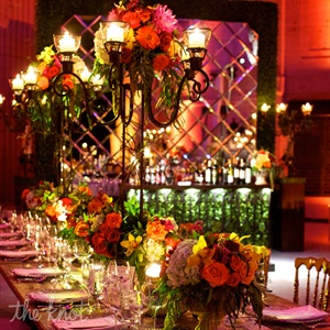 At their second celebration, wrought-iron details, scrolling candelabras, a colorful mix of flowers, wooden farm tables and a boxwood-hedge bar lent the dining area the feel of a French park.