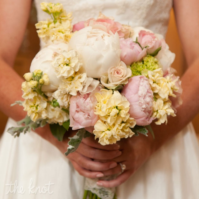 "Courtney's bridal bouquet was created from ivory peonies, which she absolutely loves, mini green hydrangeas, blush roses and blush ranunculuses. Courtney had the bouquet wrapped in lace and tied with an antique brooch for a touch of ""southern charm meets vintage""."