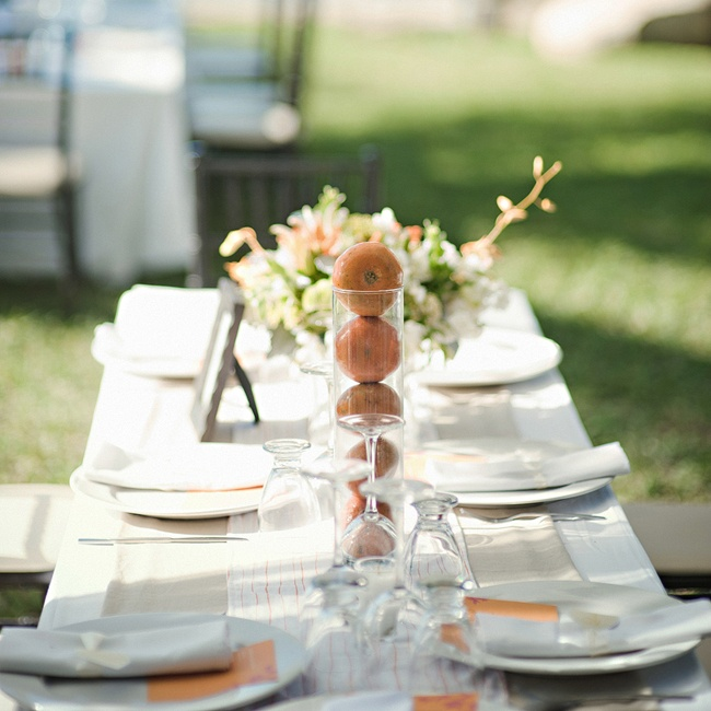 Lindsay and Brady wanted their tables to look elegant but they didn't want them to compete with the natural beauty of the site. They chose simple white and cream linens and accentuated the tables with vases of tangerines and white, green and orange floral centerpieces.