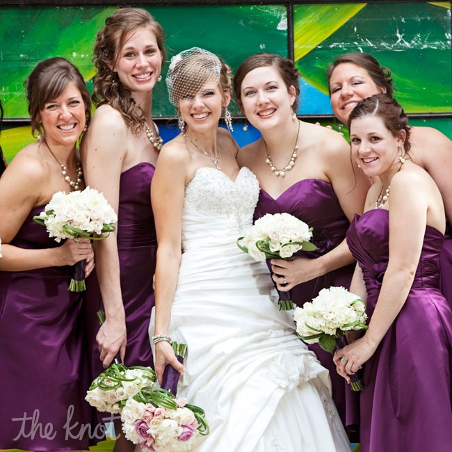 Jenni's bridesmaids wore plum dresses with champagne heels and carried ivory bouquets and vintage-inspired necklaces.