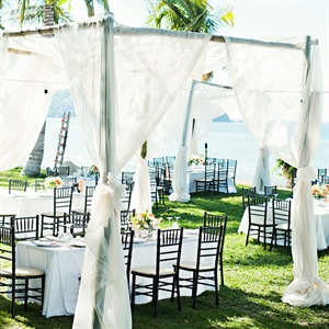 To create a romantic ambiance, the tables were placed under wooden structures draped in fabric.