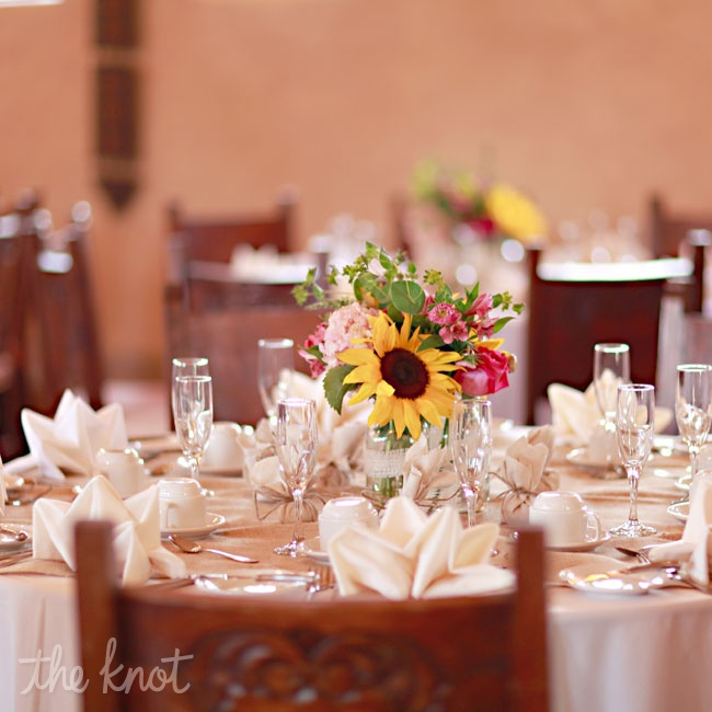 Gracie's favorite flower is the sunflower, so they decided to use yellow as the accent color for the décor. The centerpieces were three mason jars tied together with burlap ribbon. The table linens were white with wide burlap runners. Right outside the reception space, guests were served a black and blue mojito with fresh berries, their signature d ...