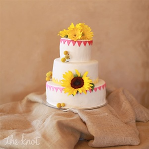 Gracie and Jim had a three-tier, white fondant with pink and yellow accent trim cake decorated with fresh flowers. Each layer was a different flavor starting with the bottom layer as strawberry champagne, the second layer was lemon with lemon filling and the top layer, a surprise to the groom, was white funfetti cake.