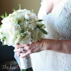 Wrapped in extra lace from her gown, Julia's all-white bouquet featured hints of greenery.