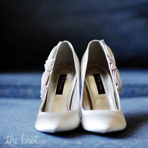 Stylish pleated accents enhanced the bride's classic white satin pumps.