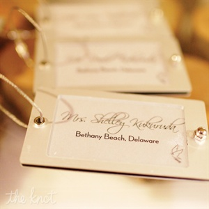 Doubling as luggage-tag favors, the escort cards were labeled with the names of cities the couple had visited together.