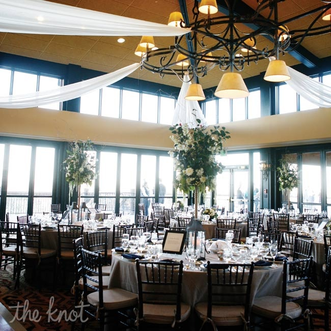 Towering green-and-white centerpieces rose like elegant trees from round tables covered in burlap linens.