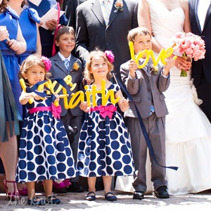 For something unexpected, the couple&#39;s flower girls and ring bearers carried bright-yellow custom signs down the ceremony aisle.