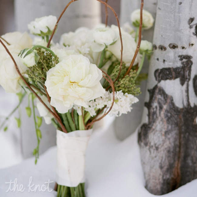 Curved willow branches and textured greens brought an organic feel to the nearly all-white bouquet of ranunculus and phalaenopsis orchids.